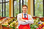 Portrait of supermarket store manager in front of fresh vegetables
