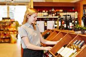 Young saleswoman in supermarket organizing bottles in wine department