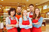 Team of five happy salespeople together in a supermarket with their arms crossed