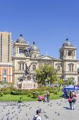 LA PAZ, BOLIVIA, MAY 8, 2014:   People walk at Plaza Murillo (monument of Pedro Domingo Murillo and Cathedral in background)