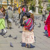 LA PAZ, BOLIVIA, MAY 8, 2014:  Local woman in traditional attire with a baby on her back walks at Plaza Murillo