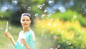 beautiful girl blowing bubbles outdoors
