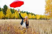 The Girl With A Red Umbrella In Autumn Park