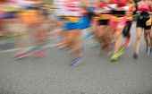 stock photo of competing  - blurred marathon athletes legs running on city road - JPG