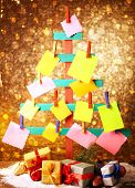 Wooden hand made fir tree with empty papers and Christmas decor on shiny background