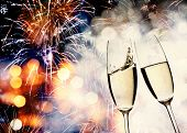 New Year's - toasting with champagne glasses against fireworks and holiday lights