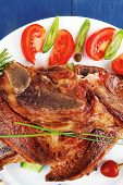 fresh grilled beef meat fillet on white plate with tomatoes and red pepper over blue wood table