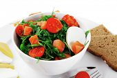 green salad with salmon and tomatoes in white bowl