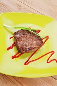 meat food : roasted fillet mignon on green plate with chives and ketchup over wooden table
