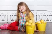 little cute girl with lemons in two yellow buckets