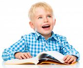 Cute little child play with book while sitting at table, isolated over white