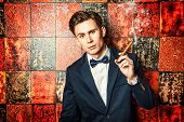 Handsome young man in elegant suit smoking a cigar.