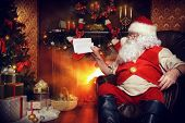 Santa Claus reading letters from children. He is at home, decorated for Christmas. Santa's mail.