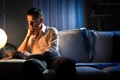 foto of boredom  - Businessman working overtime late at night in the living room with tablet and paperwork - JPG