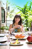 Beautiful young spanish woman smiling by the dining table, about to have a meal, outdoor home environment