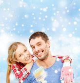 repair, building, love and people concept - smiling couple with paintbrush over blue sky, snow and clouds background