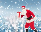 christmas, holidays and people concept - man in costume of santa claus running with gift box over snowy city background
