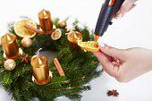 Woman Sticking Orange Hot Gun On Christmas Wreath On White Table