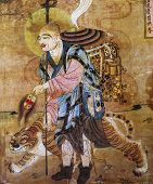 Chinese fresco of a monk and tiger in cave Dunhuang, China