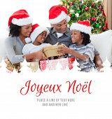 Family holding Christmas gifts against joyeux noel