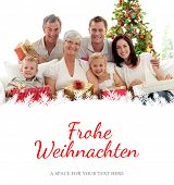 Family holding Christmas presents at home against christmas greeting in german