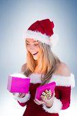 Festive blonde opening a gift on vignette background