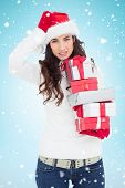 Stressed brunnette in santa hat holding gifts against blue background with vignette