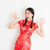 Portrait of Asian Chinese girl with surprised facial expression, in traditional red qipao standing on plain background.