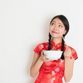 Asian Chinese female eating using chopsticks holding rice bowl, in traditional cheongsam on plain background, thinking and looking up at copy space.