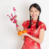 Portrait of Asian Chinese girl hands holding tangerine orange and plum blossom, in traditional red qipao standing on plain background.
