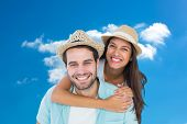 Happy casual man giving pretty girlfriend piggy back against cloudy sky