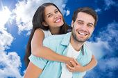 Happy casual man giving pretty girlfriend piggy back against bright blue sky with clouds