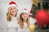 Festive mother and daughter smiling at tree against snowflake frame