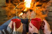 Hands with red coffee cups in front of lit fireplace against house outline