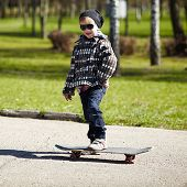 little boy with skateboard on the street