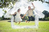 Cute couple jumping in the park together holding hands against house outline in clouds
