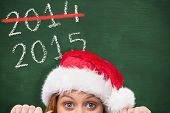 Festive redhead smiling at camera holding poster against green chalkboard