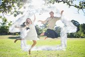 Cute couple jumping in the park together against house outline in clouds