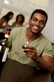 African-american Man Holiding A Wine Glass In A Restaurant