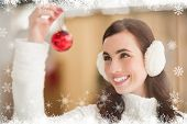 stock photo of muffs  - Pretty brunette with ear muffs holding bauble against fir tree forest and snowflakes - JPG