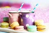 Gentle colorful macaroons and milk in decorative mugs on color wooden background
