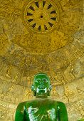 Buddha statue made of jade green. And the history of the Buddha gold background.