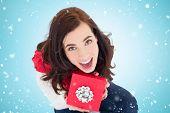 Excited brunette sitting holding red gift against blue vignette