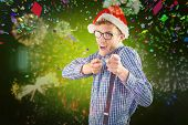 Geeky hipster wearing santa hat against colourful fireworks exploding on black background