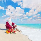 Santa Claus With Many Christmas Golden Gifts Relaxing On Tropical Beach