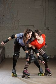 stock photo of roller-derby  - Pair of beautiful female roller derby skaters in action pose - JPG