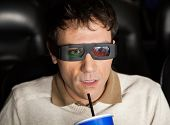 image of watching movie  - Closeup of shocked man drinking cola while watching 3D movie at cinema theater - JPG