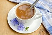 image of chicory  - Chicory drink in a white cup with a flower and a spoon - JPG