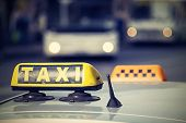 picture of headlight  - automobile emblem and sign of a taxi against city streets with the vague image of buses and the included headlights with a digital retro effect - JPG