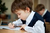 image of diligent  - Diligent preschool sitting at desk in classroom - JPG